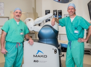 Denny A. Carter, M.D., and Beau Sasser, M.D. dressed in scrubs with the Mako robotic surgery system